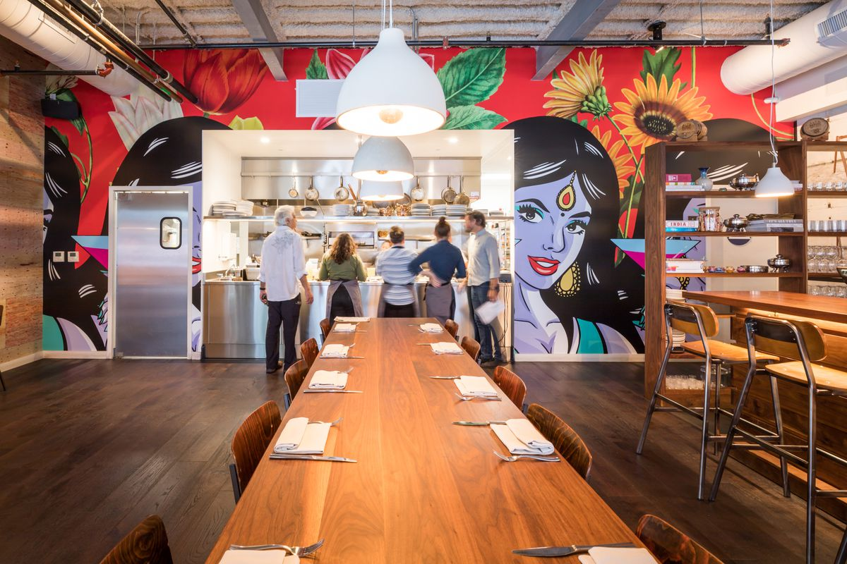 The dining room at Besharam, dominated by a bright mural