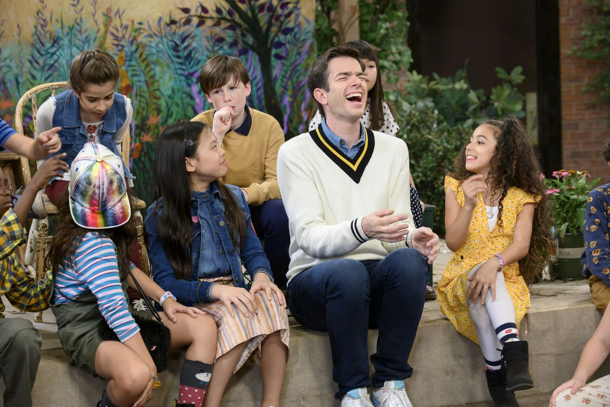 john mulaney cackles in a mister rogers sweater while sitting around his sack lunch bunch kids