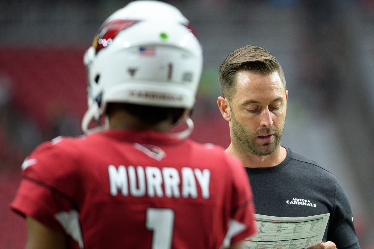 Head coach Kliff Kingsbury of the Arizona Cardinals looks at his play sheet in front of quarterback Kyler Murray warms up for the NFL game against the Seattle Seahawks at State Farm Stadium on September 29, 2019 in Glendale, Arizona.