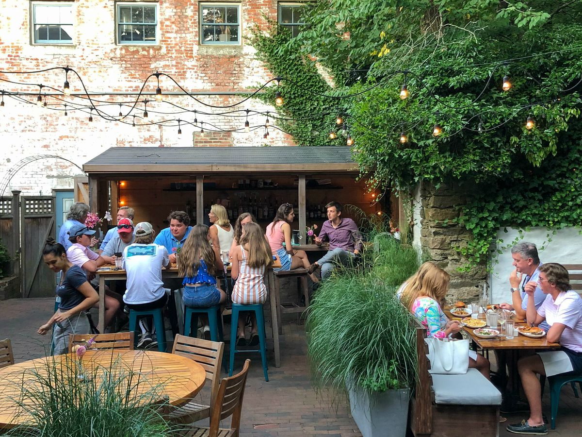 Against the backdrop of a faded brick building, the Or the Whale patio features a small covered bar and a variety of other seating options, including a sizable wooden round table. Lush greenery and string lights embellish the space.