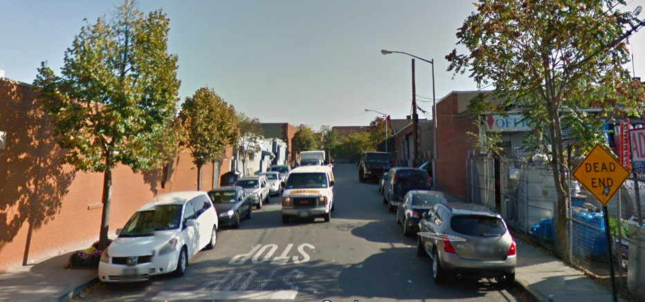 A street in Jamaica, Queens. The street has parked cars. There are buildings on both sides of the street.