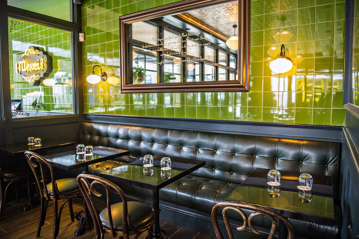 A leather booth at Bread & Butterfly, backed by a green-tile wall.