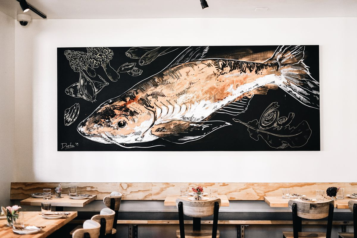 A view of a catfish mural in a light-filled dining room at the restaurant Ba Sa.