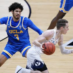 BYU guard Spencer Johnson (20) drives past UCLA guard Johnny Juzang (3) during the first half of a first-round game in the NCAA college basketball tournament at Hinkle Fieldhouse in Indianapolis, Saturday, March 20, 2021.
