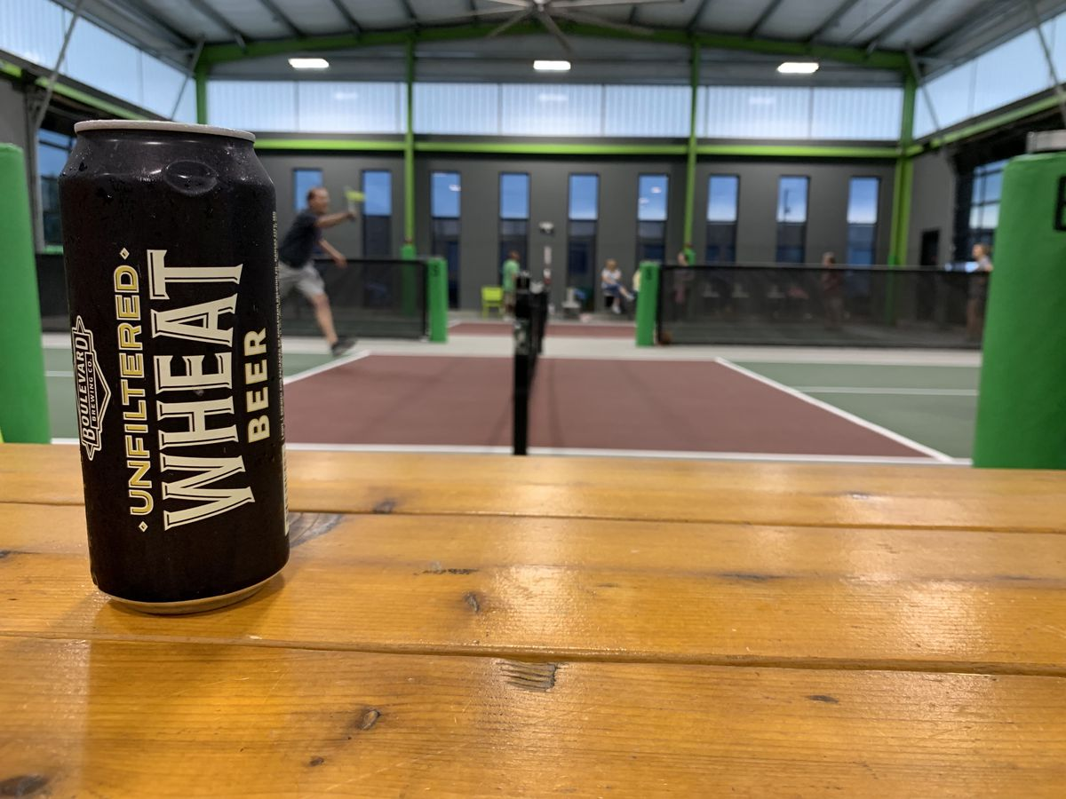 A can of Boulevard Brewing Co.'s Unfiltered Wheat beer sits on a wooden table, with a person hitting a ball on a pickleball court in the background.