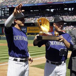 Colorado Rockies shortstop Troy Tulowitzki, left, waves to the crowd after being awarded the Gold Glove trophy for 2011, before the Rockie' baseball game against the San Francisco Giants in Denver on Monday, April 9, 2012. Holding Tulowizki's trophy is infield coach Rich Dauer.