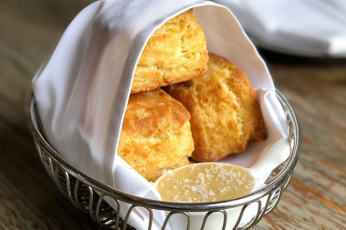 A basket of biscuits wrapped in a white napkin.
