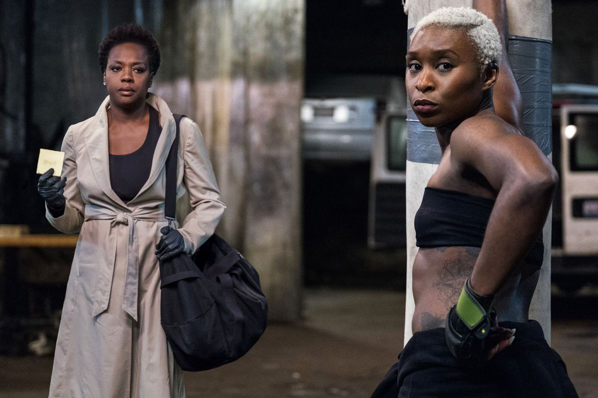 Viola Davis and Cynthia Ervio in 'Widows' looking at the camera, the former wearing a trench coat and the latter wearing a bandeau
