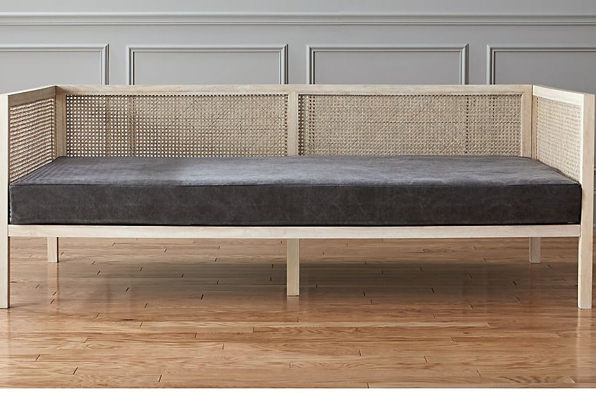 Daybed with woven back and gray cushion seat.