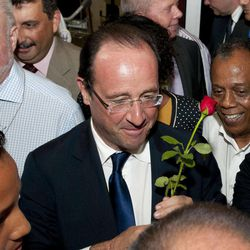 Socialist presidential candidate Francois Hollande holds a rose as he arrives at Saint-Denis de la Reunion airport in La Reunion island, Saturday, March, 31, 2012. Hollande is on a two-day campaign visit to the French island in the Indian Ocean.
