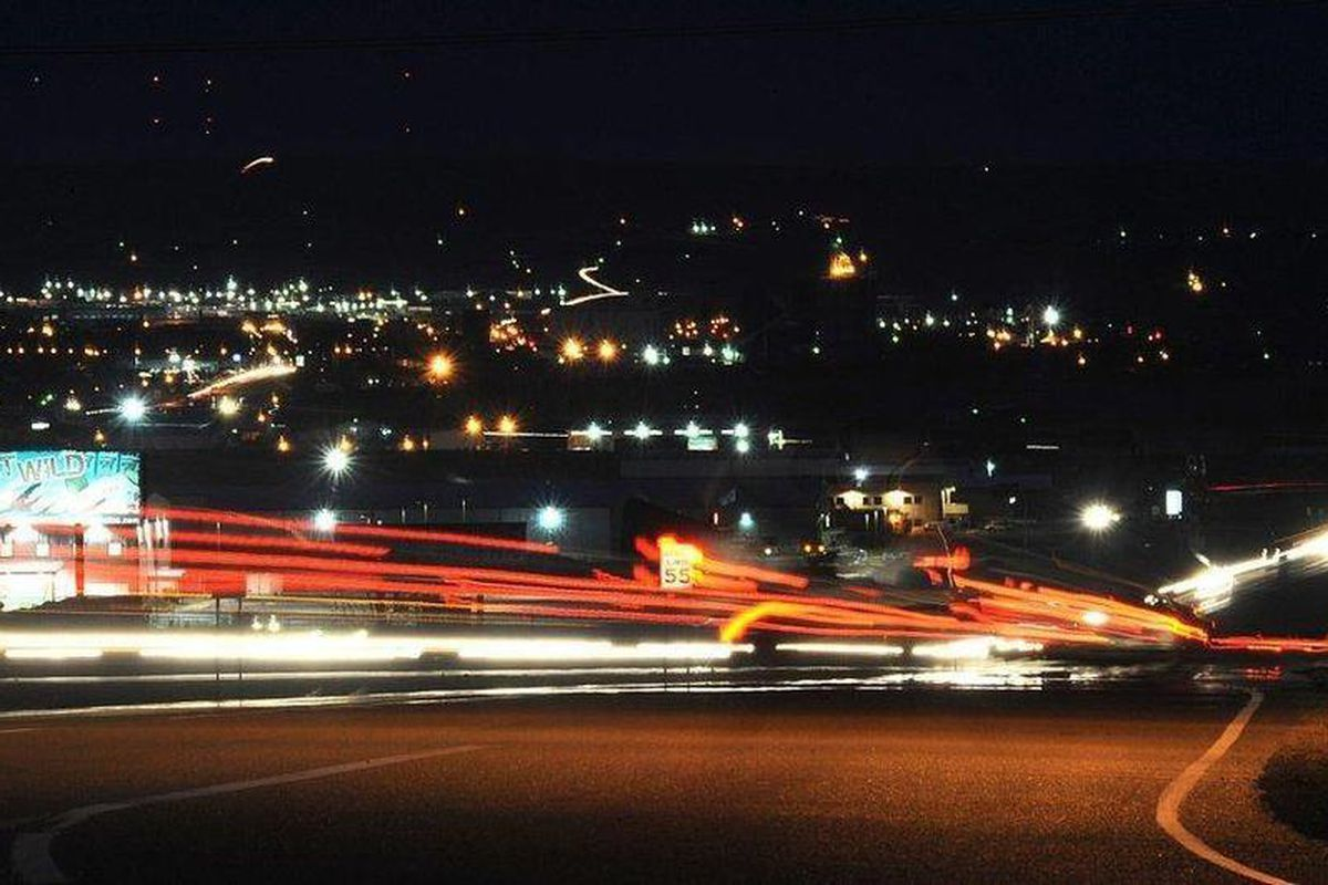 In a time exposure photo, tractor-trailers leave streaks of light as they merge onto Highway 2 west of Williston, N.D. As thousands of workers and their families move in search of jobs to North Dakota's Bakken oilfield, nearby Montana communities' resourc