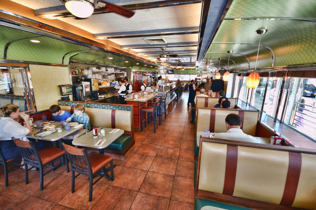 A long and narrow diner is filled with red and tan booths and a counter
