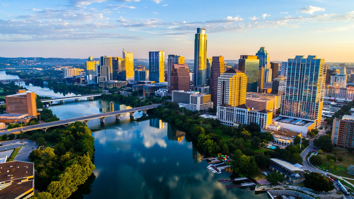 The skyline of downtown Austin, with buildings lining the shores of a river.