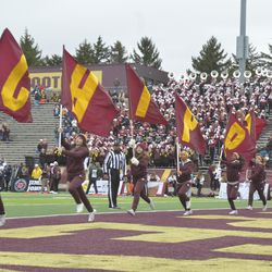 CMU cheerleaders run with the small flags after a touchdown.