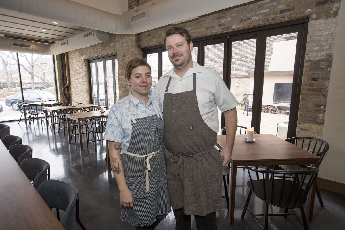 A couple of chefs in aprons standing and smiling at their dining room.
