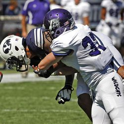 Brigham Young Cougars wide receiver Cody Hoffman (2) fumbles as he is hit by Weber State Wildcats safety Chris Wheeler (37) during the first half as Brigham Young University plays Weber State University in football  Saturday, Sept. 8, 2012, in Provo, Utah.