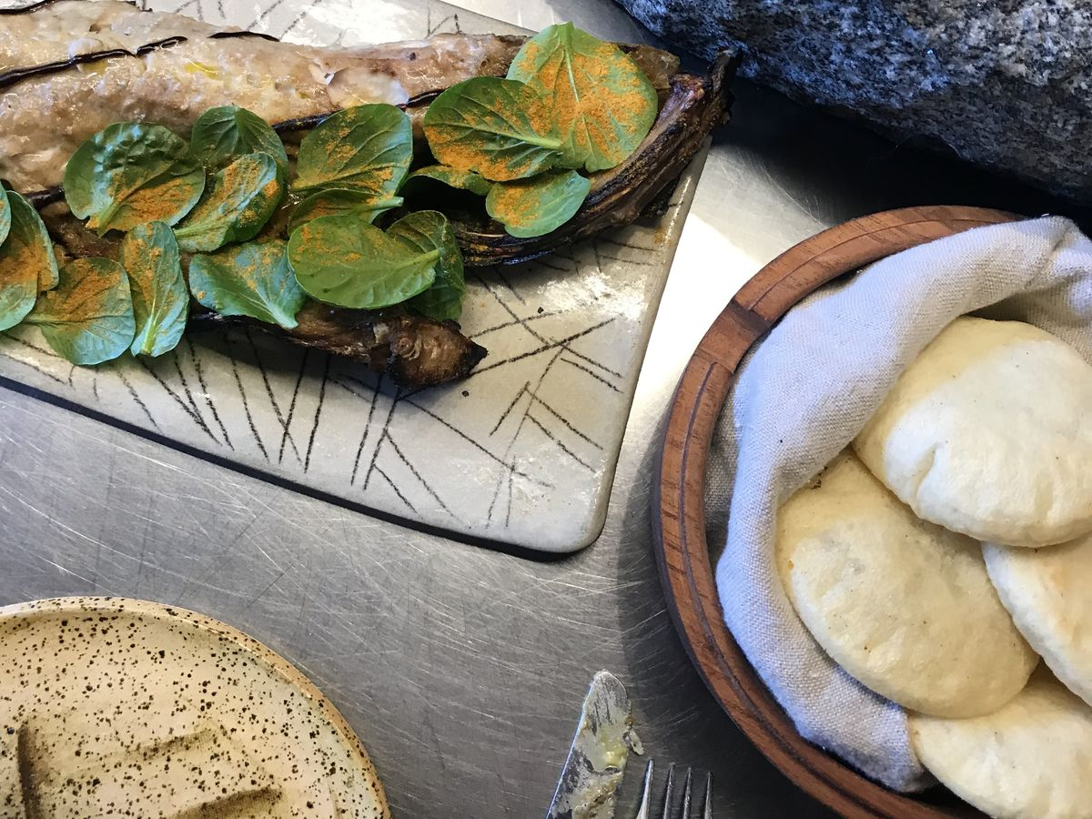 A fish artistically garnished with a row of herbs sits beside a bowl filled with fresh, puffy arepas
