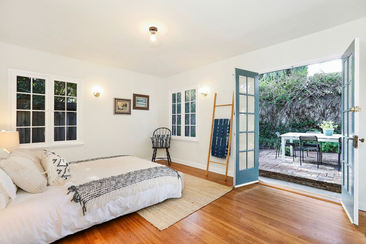 A bedroom with open French doors that lead out to a cozy patio.