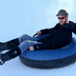 Seth Lambert tries extreme tubing down ski jump hills at Utah Olympic Park near Park City Saturday, Dec. 26, 2015, in Synderville Basin.