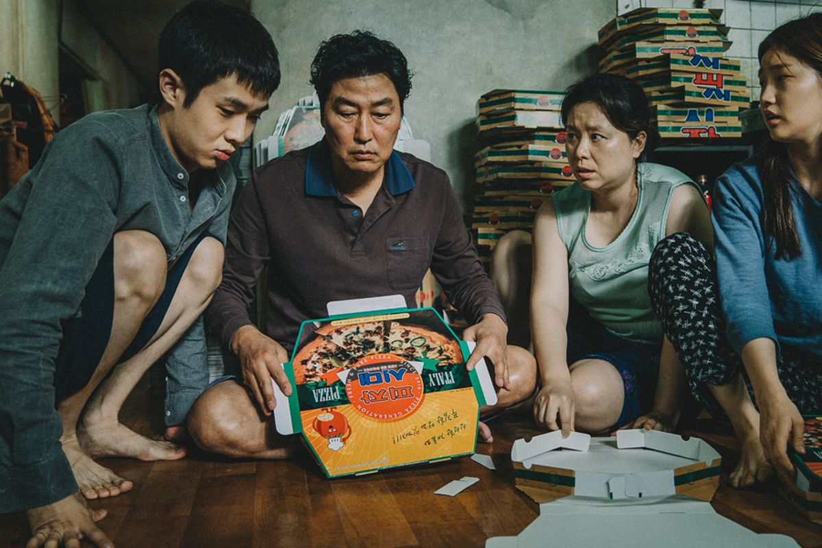 A scene from the South Korean film Parasite in which the characters sit on the floor of their crowded apartment and assemble pizza boxes.