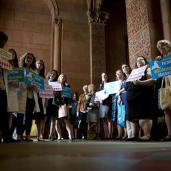 Reproductive rights advocates hold signs during a news conference at the state Capitol on Tuesday, May 24, 2016, in Albany, N.Y. (AP Photo/Mike Groll)