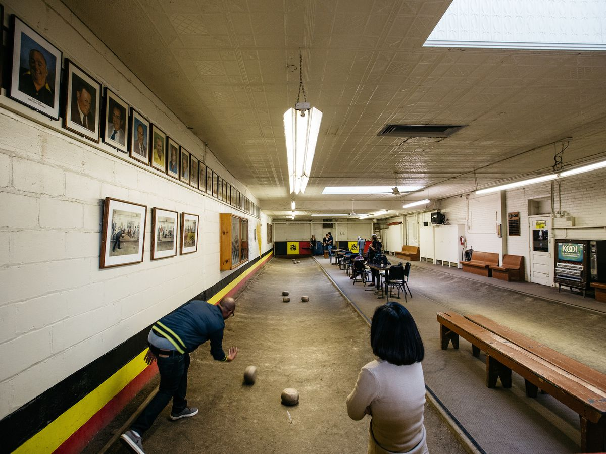 People roll wheels in dirt feather bowling lanes at Cadieux Cafe.