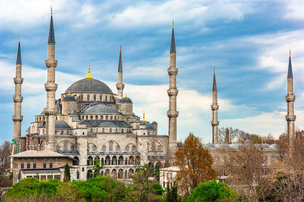 """The exterior of the <span data-author=""""843"""">Blue Mosque in Turkey. The facade is tan and there are blue tiles that line the interior walls and roof.</span>"""