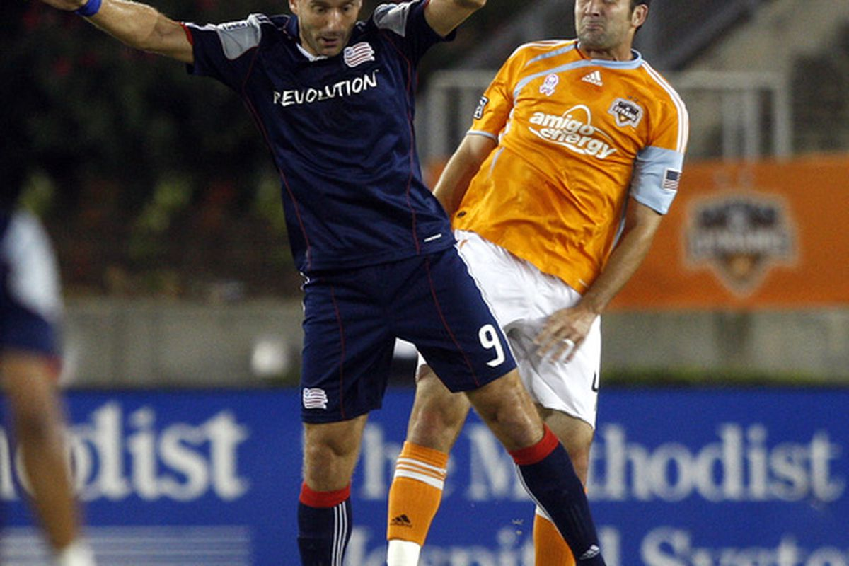 HOUSTON - OCTOBER 10:  Ryan Cochrane #4 of the Houston Dynamo heads the ball away from Ilija Stolica #9 of the New England Revolution in the firs half at Robertson Stadium on October 10, 2010 in Houston, Texas.  (Photo by Bob Levey/Getty Images)
