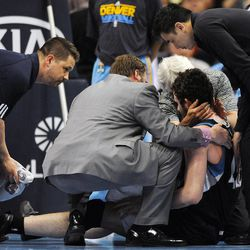 Trainers look at Minnesota Timberwolves power forward Kevin Love after he was hurt in a collision in the first quarter of an NBA basketball game against the Denver Nuggets in Denver, Wednesday, April 11, 2012.