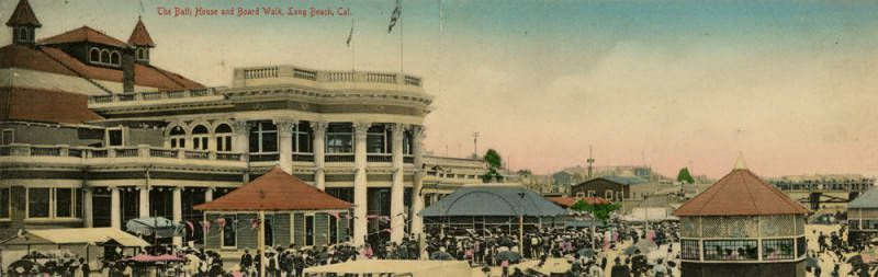 A colorful vintage postcard of a crowded boardwalk with a large colonial-style bathhouse. The boardwalk is populated with smaller structures, including a gazebo.