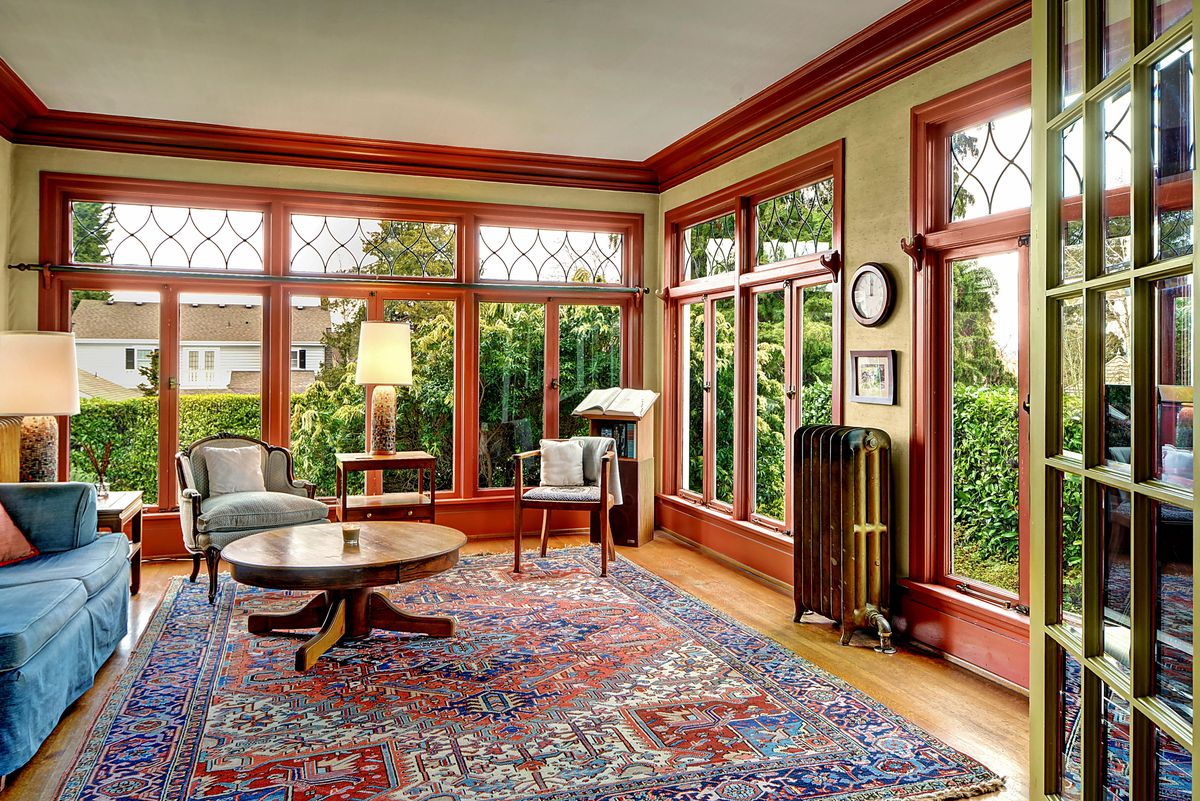 A living room with floor-to-ceiling, leaded glass windows and wood trim
