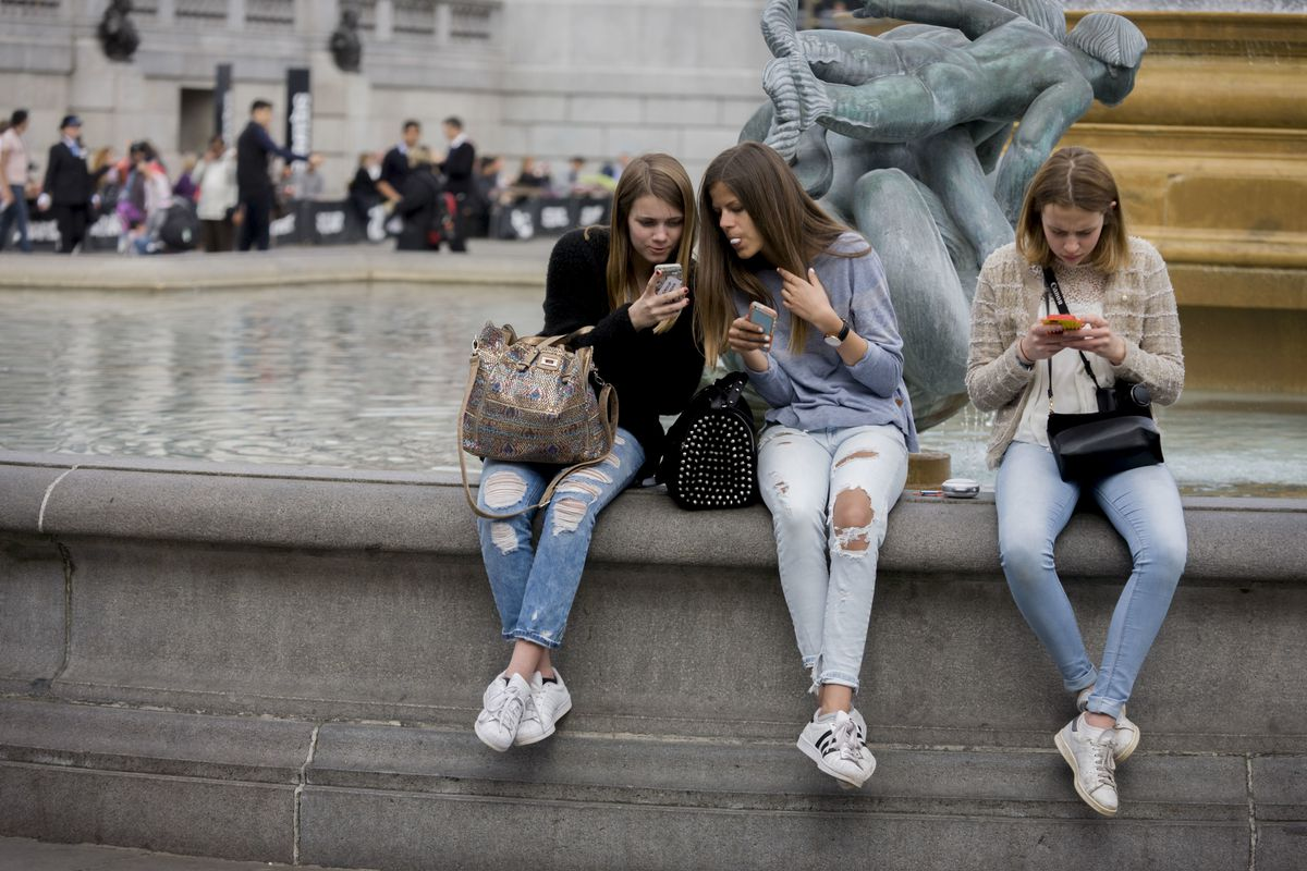 Three teenage girls look at their phones while sitting beside a fountain in London.