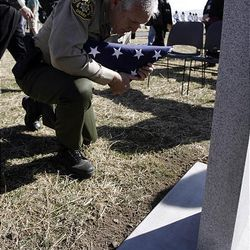 Salt Lake County Sheriff Jim Winder kneels with a flag in front of a grave marker for deputy James D. Hulsey, who was killed in the line of duty in 1913. Winder was taking part in a ceremony Monday for Hulsey in the Bingham City Cemetery.