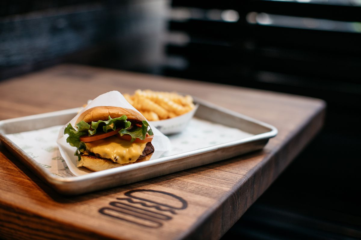 A shack burger on a metal tray on a wood table next to a basket of crinkle cut fries.