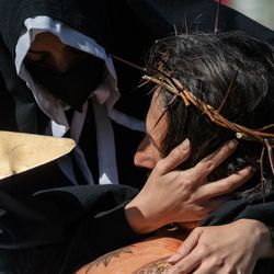 Nancy Ayala, who plays Mary, cradles Isaac Bucio, who plays Jesus Christ, during Via Crucis on the field of St. Procopius Catholic Church in Pilsen, Friday morning, April 2, 2021. The annual Via Crucis is a Good Friday tradition that reenacts the Stations of the Cross, a Catholic devotion that recounts Jesus' passion and death.