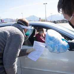 A Project Protect volunteer picks up a bag of materials to make clinical face masks for the state's health care workers in Murray on Tuesday, April 14, 2020.