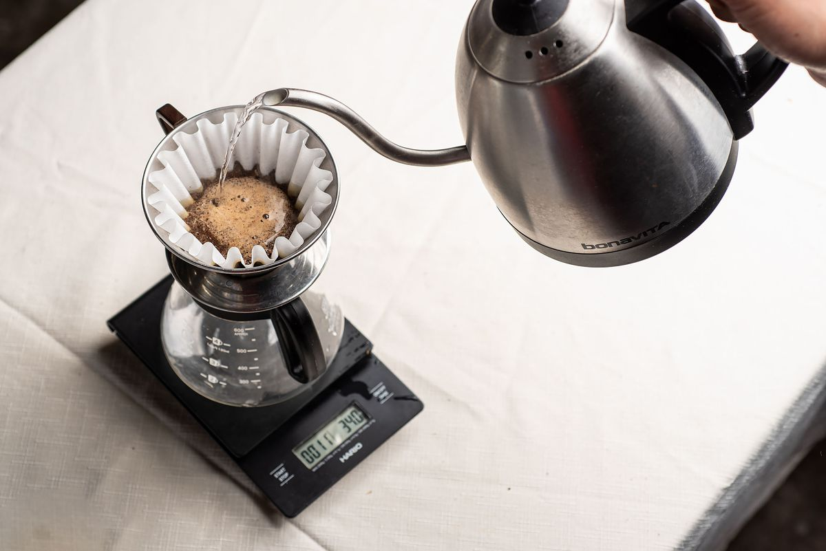Water is poured from a kettle into a Kalita brewer which is sitting on top of a carafe.