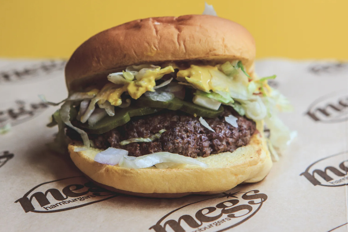 A burger filled with toppings and sauce on a placemat that says Meg's Hamburgers