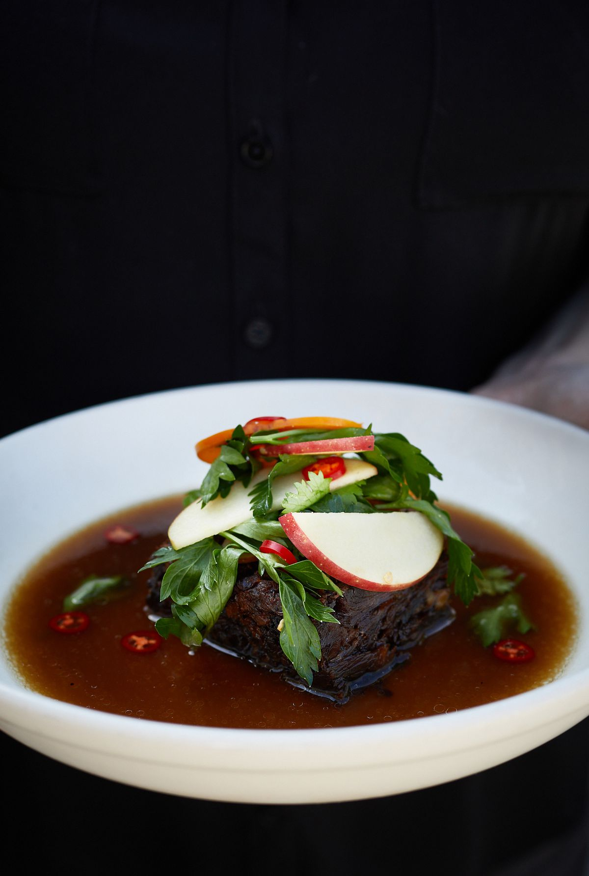A white bowl filled with a dark brown broth with a cut of boar meat in the middle that is topped with sliced apples and leafy greens
