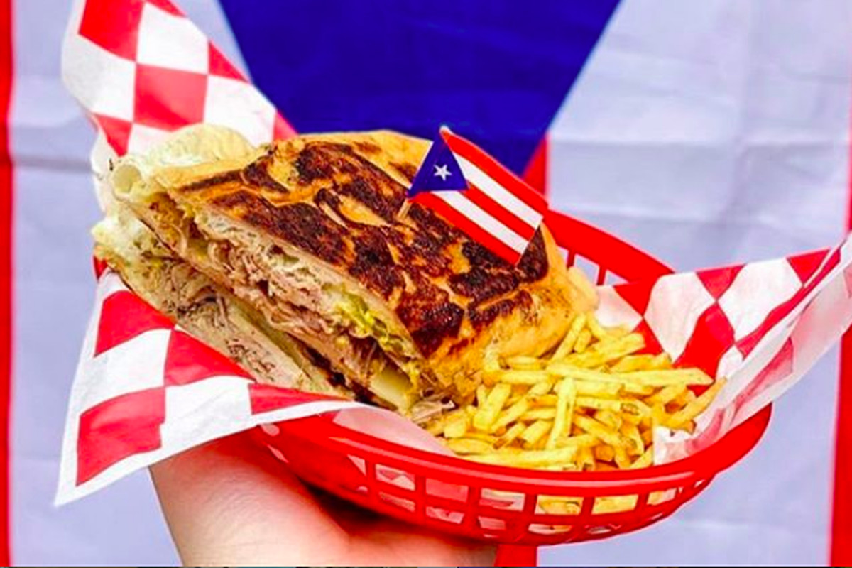 A hand holding a red basket containing a Mr. Pig sandwich with slow-roasted pernil, Swiss cheese, mustard, mayo, and pickles on a pan sobao