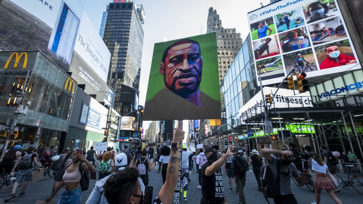 """Protesters wearing masks walk through the streets of Times Square holding up their hands and chanting, """"Hands Up Don't Shoot"""" after police officers conceded to let protesters that are trying to peacefully march through Times Square with one protester holding a sign with a portrait painting of George Floyd."""