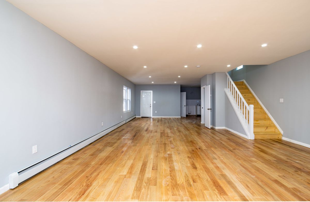 A living area with grey walls, hardwood floors, and a staircase.