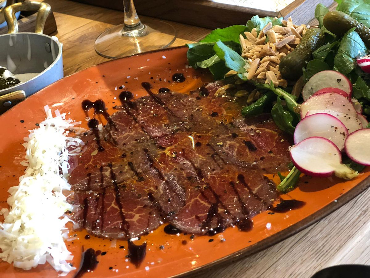 A long bright plate spread with beef carpaccio drizzled with sauce and a salad of greens, radishes and seeds