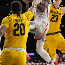 Arizona's Devonaire Doutrive, center, moves fluidly between Cal defense during the Arizona-Cal game in McKale Center on February 21 in Tucson, Ariz.