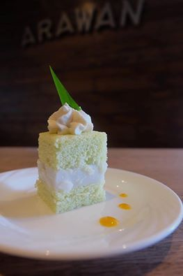 A Thai dessert of Young Coconut Pandan Cake sitting in the center of a white plate