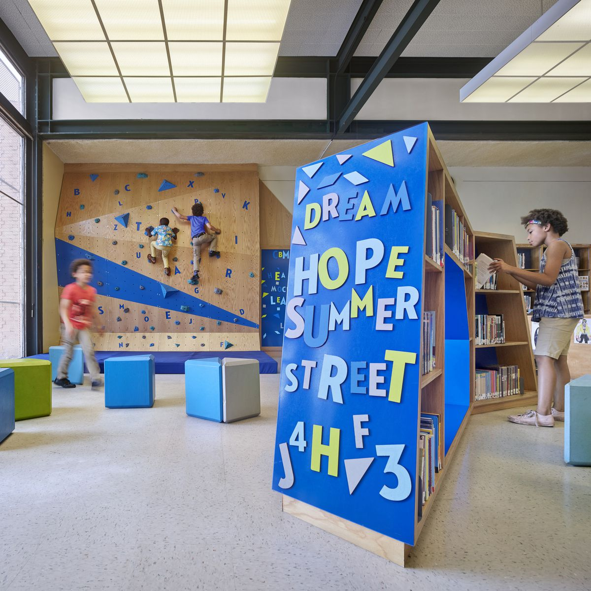 Children play on a climbing wall made of wood, with blue accents in a library. There are also blue and green decoration on the library shelves, as well as blue and green ottomans scattered in the space.