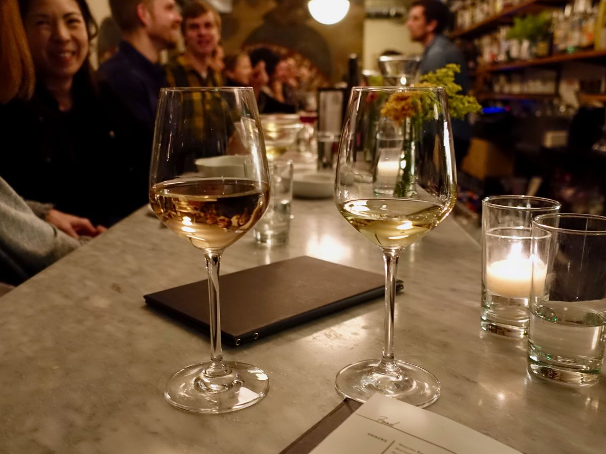The glasses of light-colored wine on a candlelit table at Baker's.