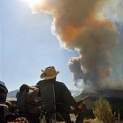 Monica Hagan and Brent Prince watch the fire from the top of Little Mountain on Sunday. Eleven structures burned over the weekend, but no injuries have been reported.