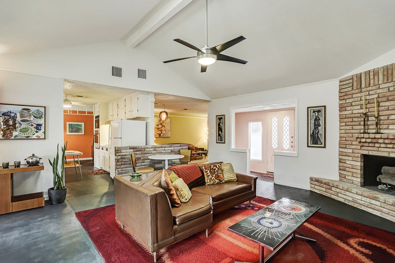 A living rom has a leather couch on a bright red rug in front of a corner brick fireplace.