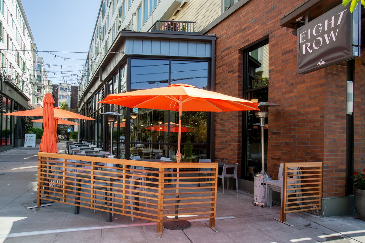 A view of the Eight Row sign and outdoor patio, with orange umbrellas and wood fencing. The restaurant has exposed brick on the outside.